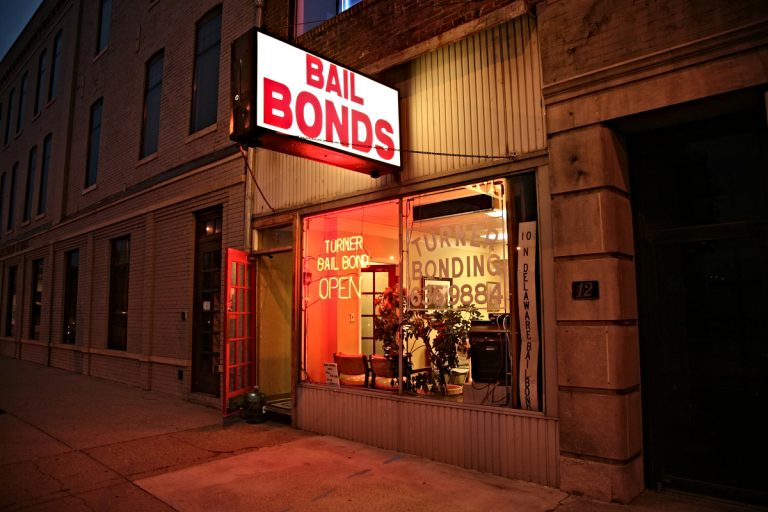Dramatically lit color photo of a bail-bonds storefront whose door is propped open with a large water cooler jug