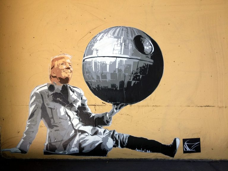 Photo of a graffiti stencil in Hamburg, Germany, by artist Marshal Arts, depicting Donald Trump dressed in an outfit from an Empire officer in 'Star Wars, holding a replica of the Death Star in one hand