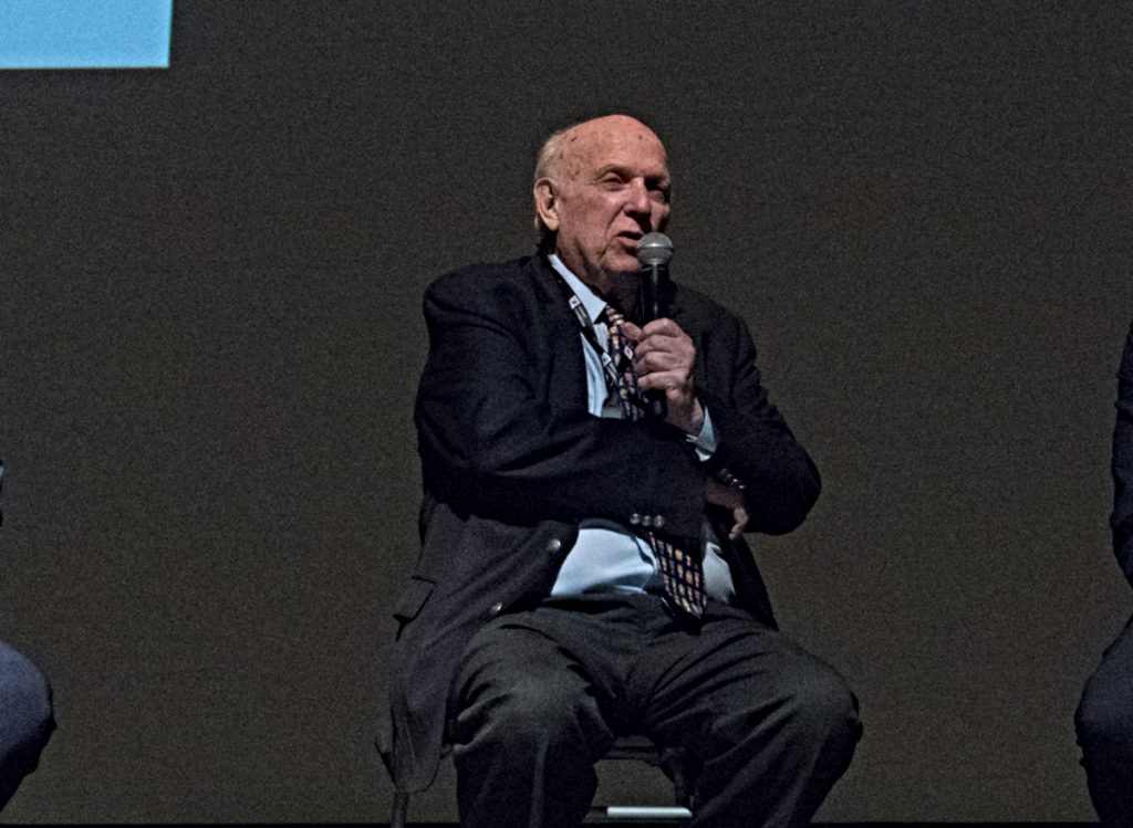 Photo aof a bald older gentleman in rumpled suit and tie, sitting on a stage, speaking into a microphone.