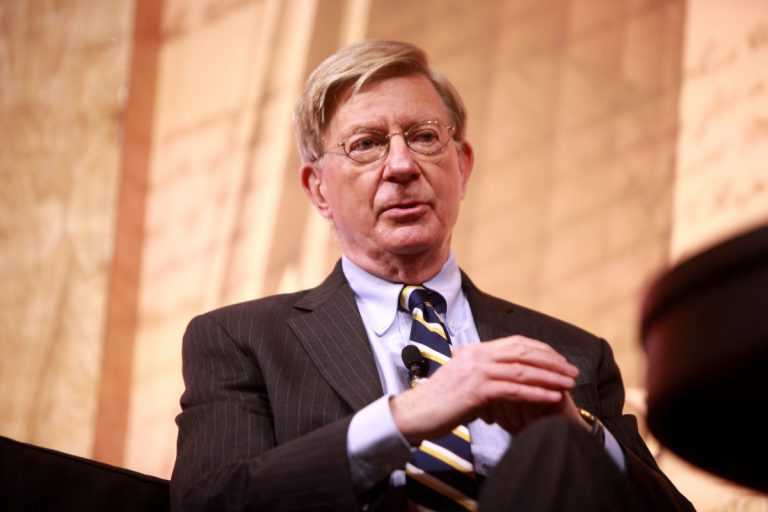 Political commentator George Will, seated, in a suit, speaking.