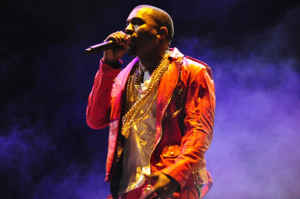 Photo of Kanye West, dressed in a jacket, T-shirt and gold chains, rapping into a mic.
