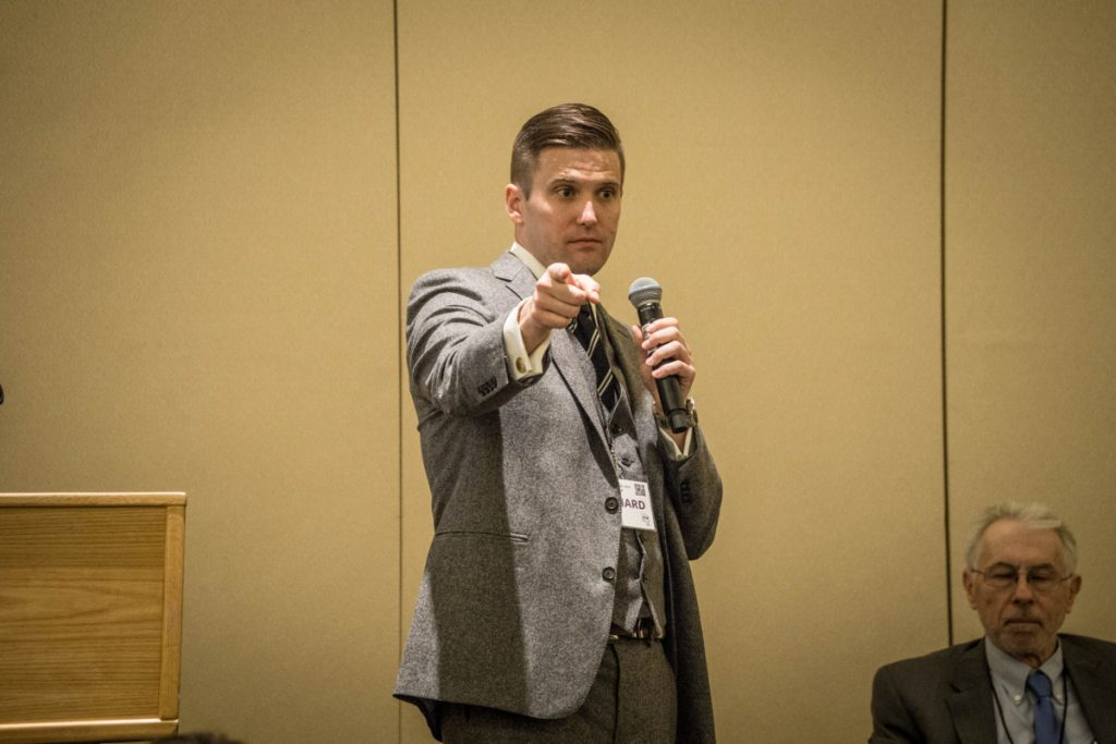 White nationalist Richard Spencer in a three-piece suit, holding a microphone at seminar, pointing.