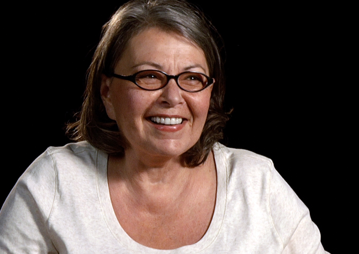 color photo of Roseanne Barr, wearing a T-shirt and glasses, smiling