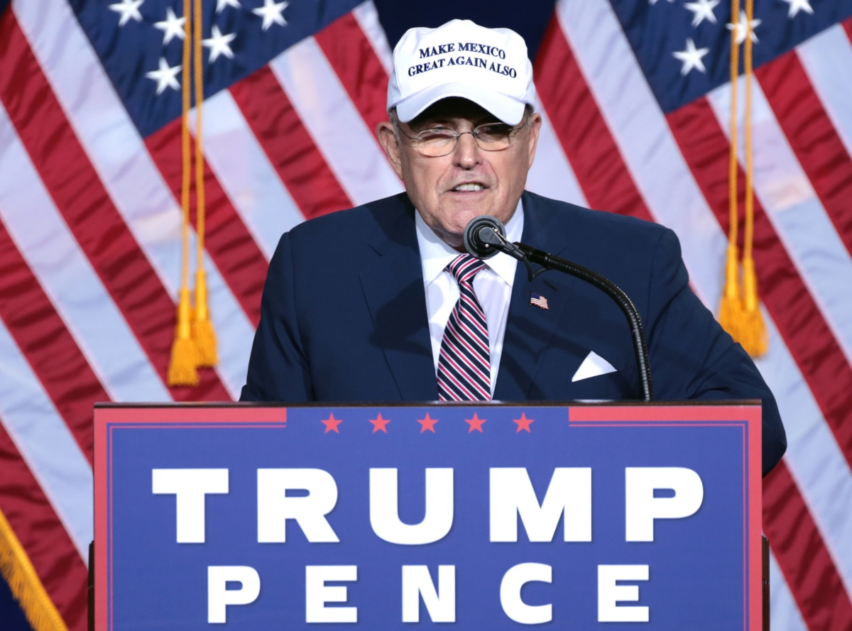 photo of Rudy Giuliani behind a lectern at a Trump/Pence rally, wearing wire-rimmed glasses and a white 'Make Mexico Great Again Also' baseball cap
