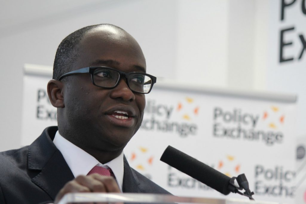 Color photo of United Kingdom Universities and Science Minister Sam Gyimah, a black man with close-cropped hair and black horn-rimmed glasses, speaking into a microphone at a lectern