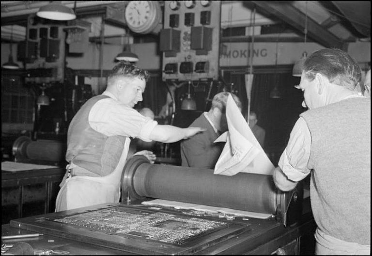 Black-and-white photo of two men working on a printing press at 'The Daily Mail' in wartime London, U.K., 1944