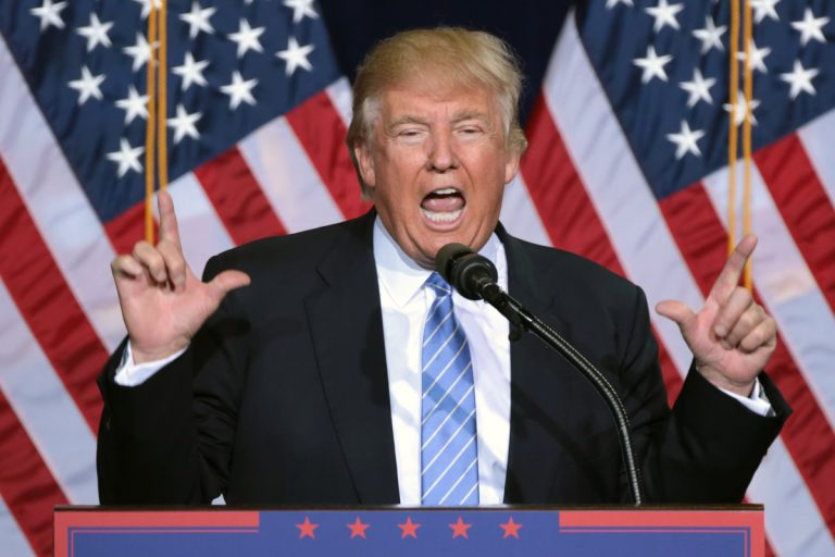 Photo of Donald Trump at a rally, speaking at a lectern with his hands in the air and two American flags behind him