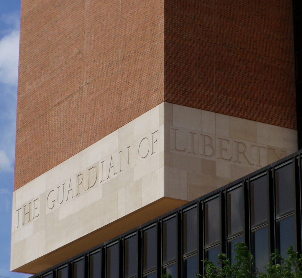 Photo of exterior detail of a corner of the James A. Byrne United States Courthouse in Philadelphia, Pennsylvania, showing the words 'The Guardian of Liberty' etched in stone