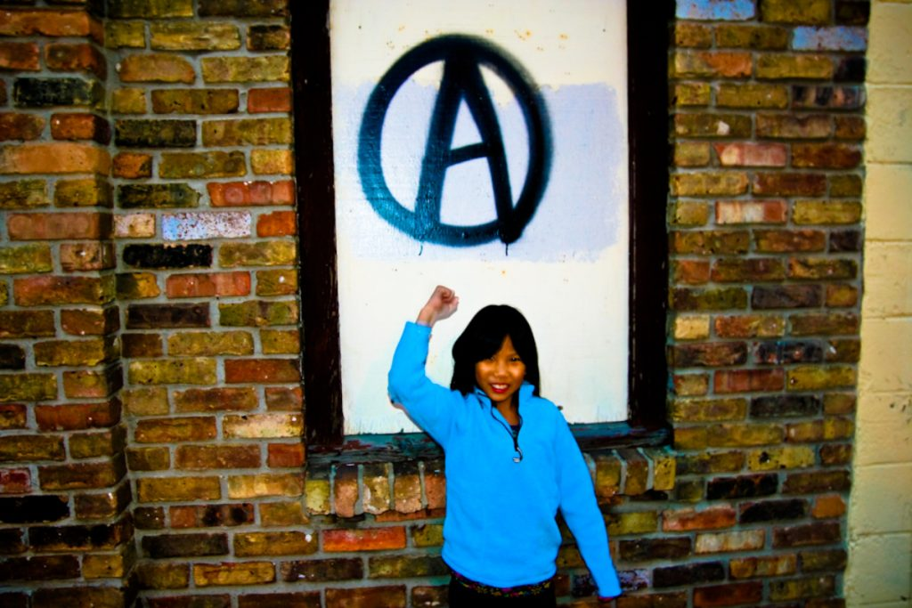 Photo of Asian girl giving fist salute in front on anarchy symbol painted in black on white background.