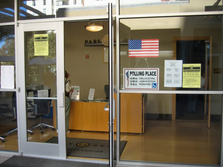 "Photo of a polling place in a storefront, with glass windows and doors, and signs posted saying ""Polling Place"" in english and other languages."