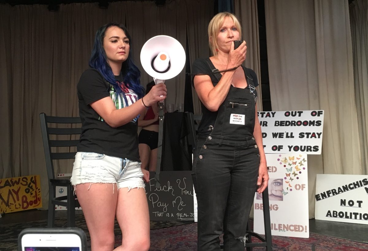 Photo of a woman on a stage speaking into a microphone attached to a bullhorn, held by another woman.