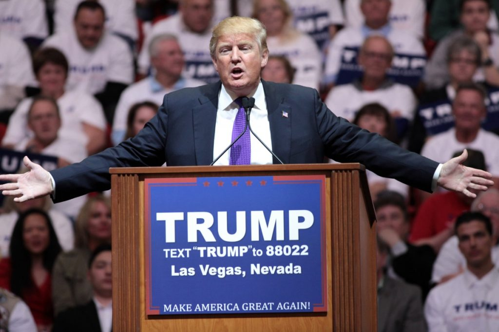 Photo of Trump at a rally behind a podium, with arms outstretched.