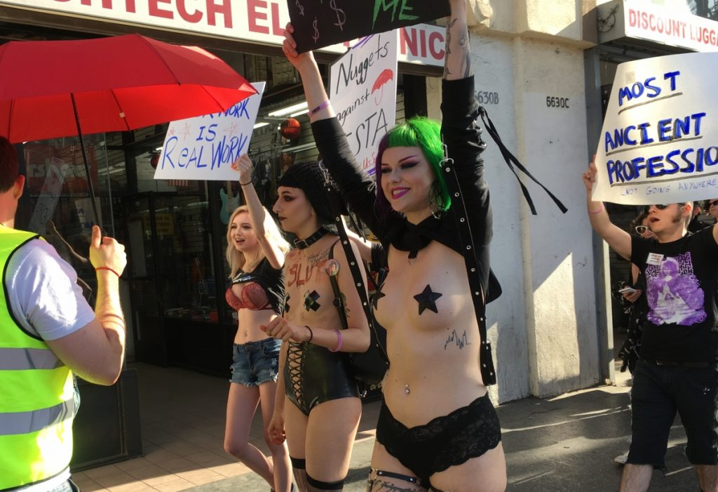 Photo of women demonstrators holding signs, two of whom are topless save for pasties or black tape over their nipples.