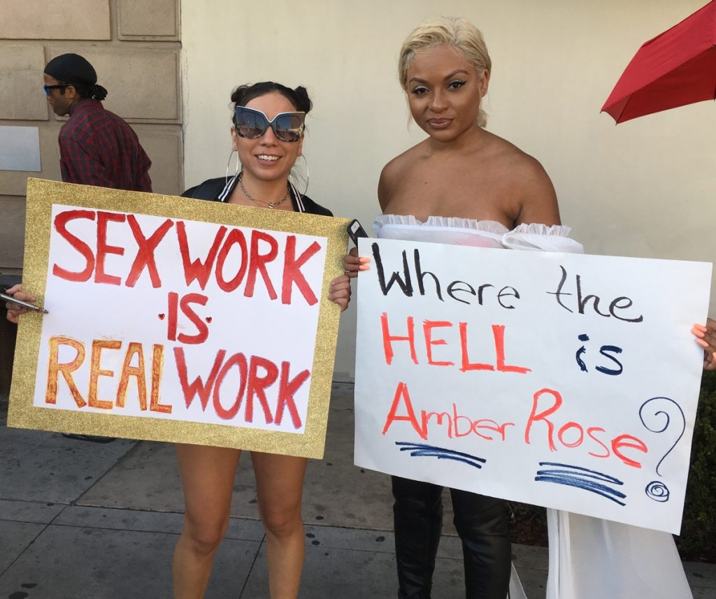 "Image of two women holding signs, one reading ""Sex Work Is Real Work,"" and the other reading, ""Where the Hell Is Amber Rose?"""