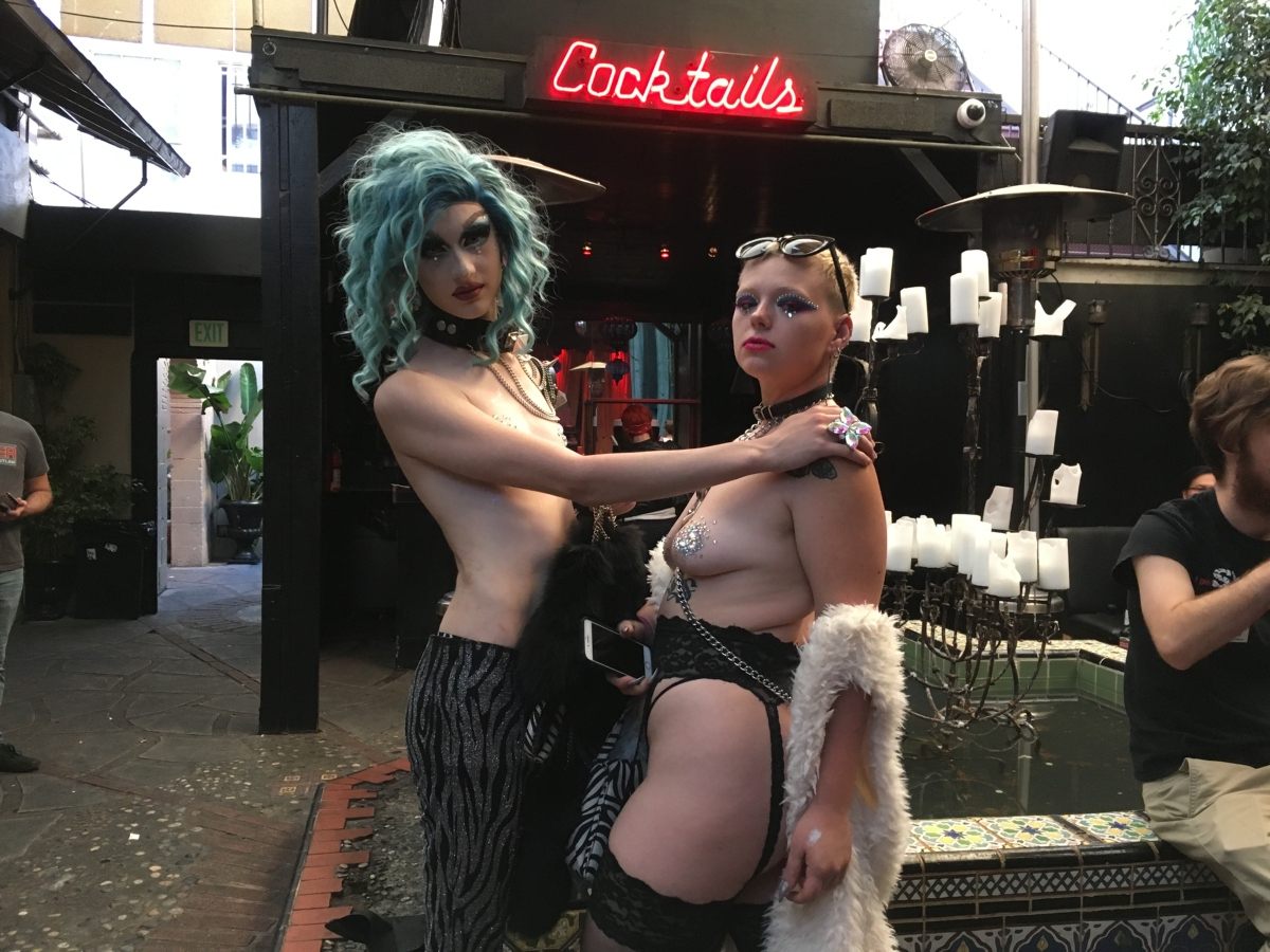 Image of a half-naked, glammed-up couple outside on a club patio in Hollywood.