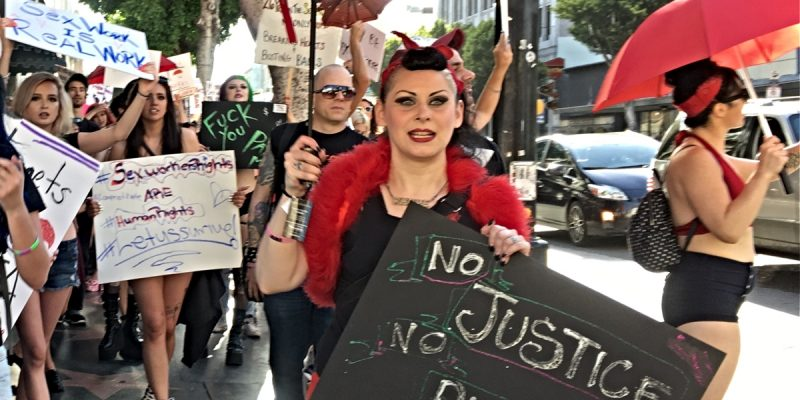 "Photo of a woman holding a red umbrella and a sign that says, ""No Justice, No Piece."""