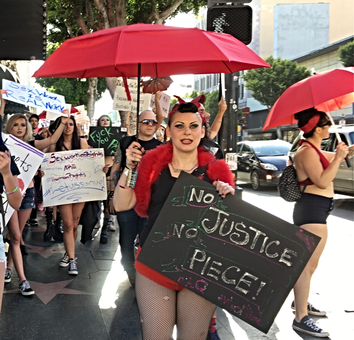 """Photo of a woman holding a red umbrella and a sign that says, """"No Justice, No Piece."""""""