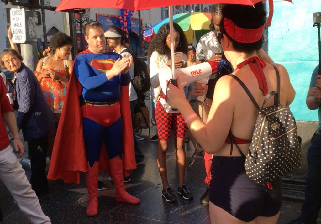 Photo of a man in a Superman outfit on a street corner applauding demonstrators.