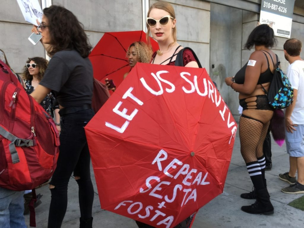 Photo of demonstrators, with one woman holding a red umbrella that reads, 'Let Us Survive: Repeal SESTA and FOSTA'