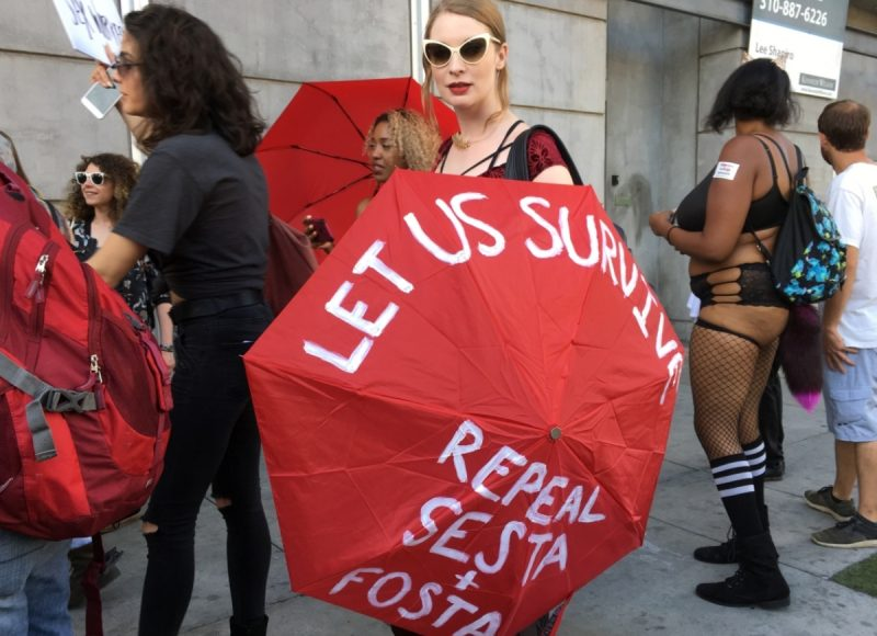 "Photo of demonstrators, with one woman holding a red umbrella that reds, ""Let Us Survive: Repeal SESTA and FOSTA"""