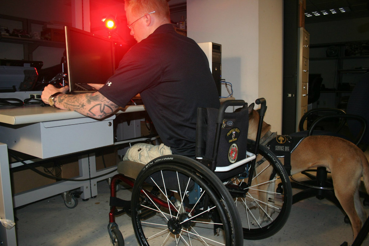 photo showing Justin Gaertner, a heavily tattooed combat-wounded veteran who works for U.S. Immigration and Customs Enforcement (ICE) at a computer workstation, with a service dog in the background