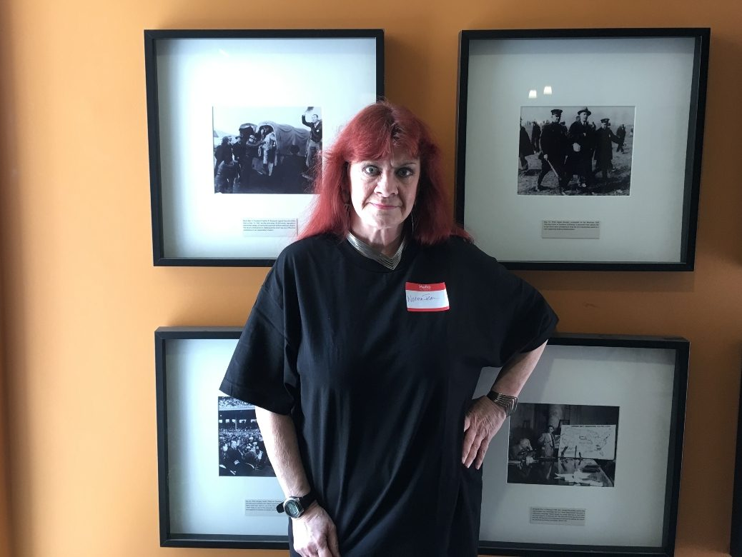 Photo of woman in a black T-shirt standing in front of a wall of black-and-white photos.