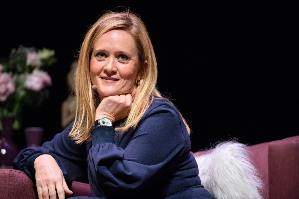 Photo of comedian Samantha Bee seated on a couch, one hand under her chin