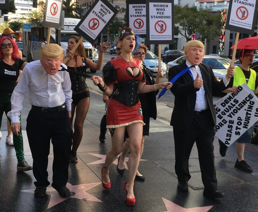 Image of a woman in a corset leading two men wearing Trump masks down a street, pulling on their ties.