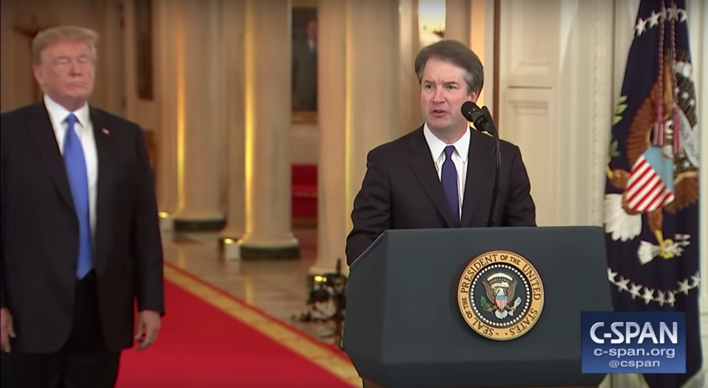 Screenshot of a middle-aged man wearing a suit and tie, speaking from a podium at the White House, with Donald Trump to his right, in background