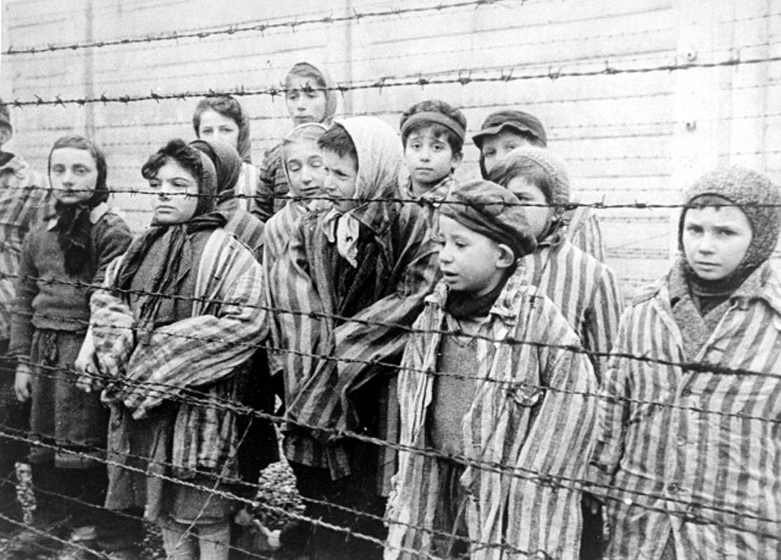 Black-and-white photo of a dozen children in concentration camp garb, taken during the liberation of Auschwitz in early 1945