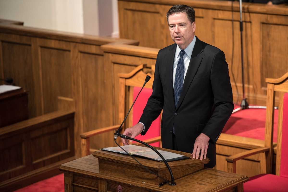 Photo of James Comey in a suit, speaking from the pulpit of the historic 16th Street Baptist Church in Birmingham, Alabama on May 25, 2016