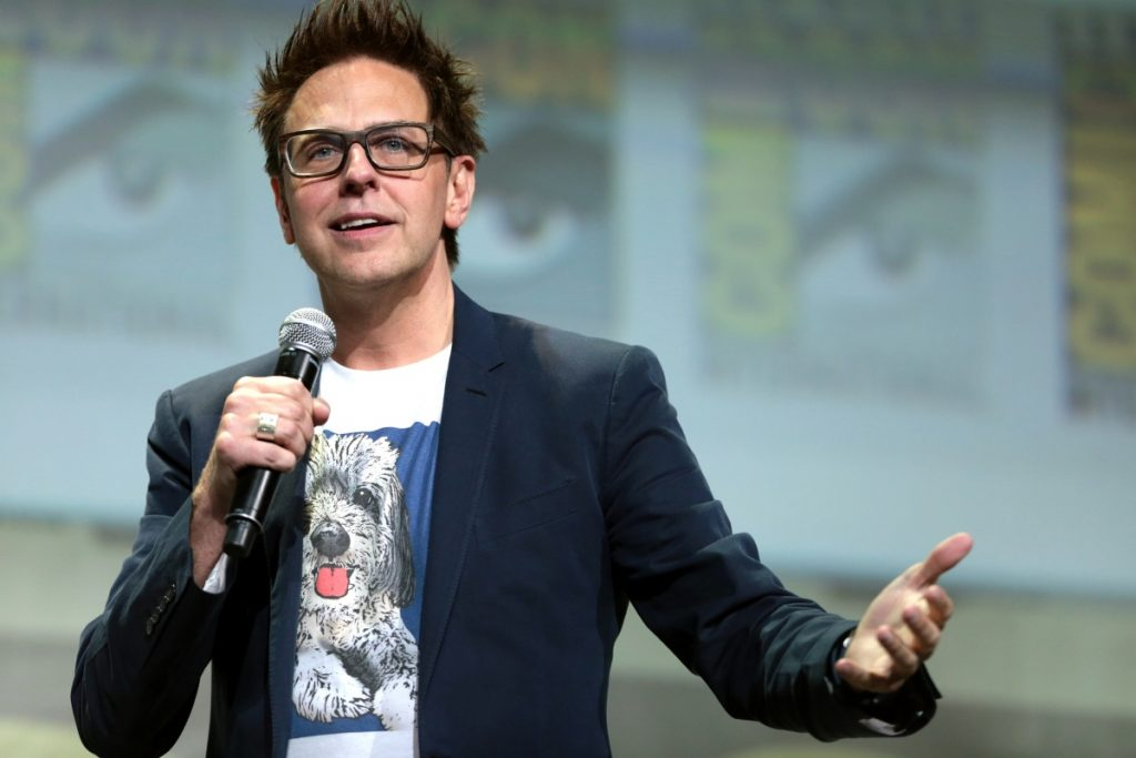 Photo of James Gunn wearing a sports coat over a T-shirt with a dog on it, speaking into a microphone held in his right hand and gesticulating with his left.
