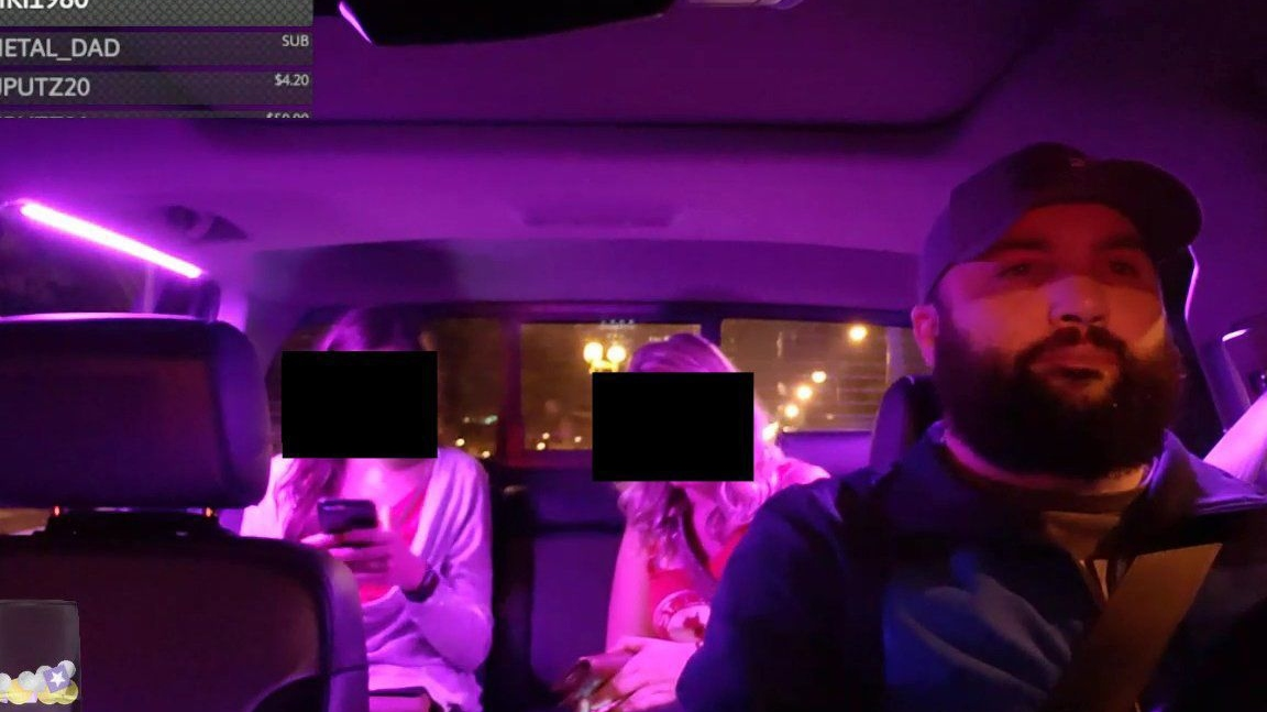 Screenshot showing the violet-lit interior of a car driven by a bearded man with two female passengers in the back seat; the passengers' faces are obscured by Photoshopped-in black squares