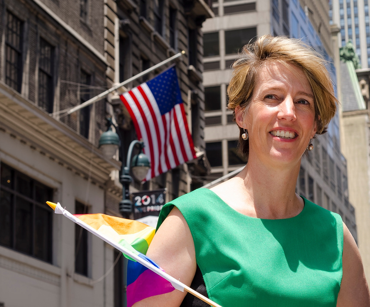 Photo of Zephyr Teachout in New York City, holding LGBT pride flag with a U.S. flag in the background.