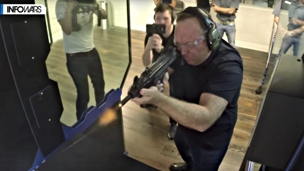 Screenshot of video showing Alex Jones firing a rifle at a gun range.