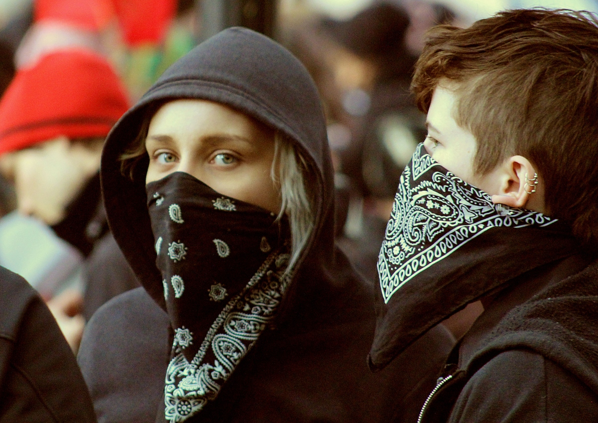 Color photo of two young demonstrators wearing black bandanas that cover their nose and mouth