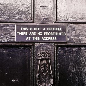 Black-and-white photo of door knocker and small sign that reads 'This is Not a Brothel There Are No Prostitutes at This Address'