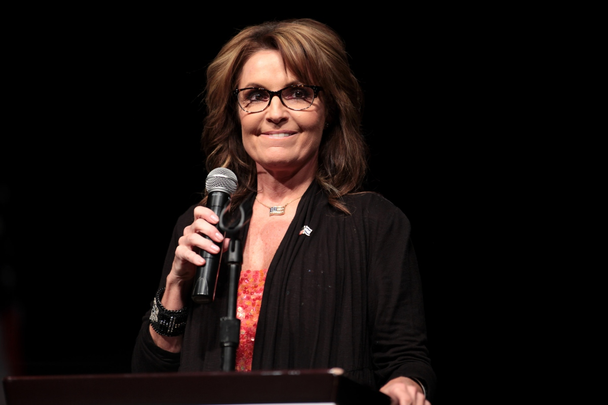 Color photo of Sarah Palin, wearing black-rimmed glasses, standing at a lectern, holding a microphone and biting her lower lip
