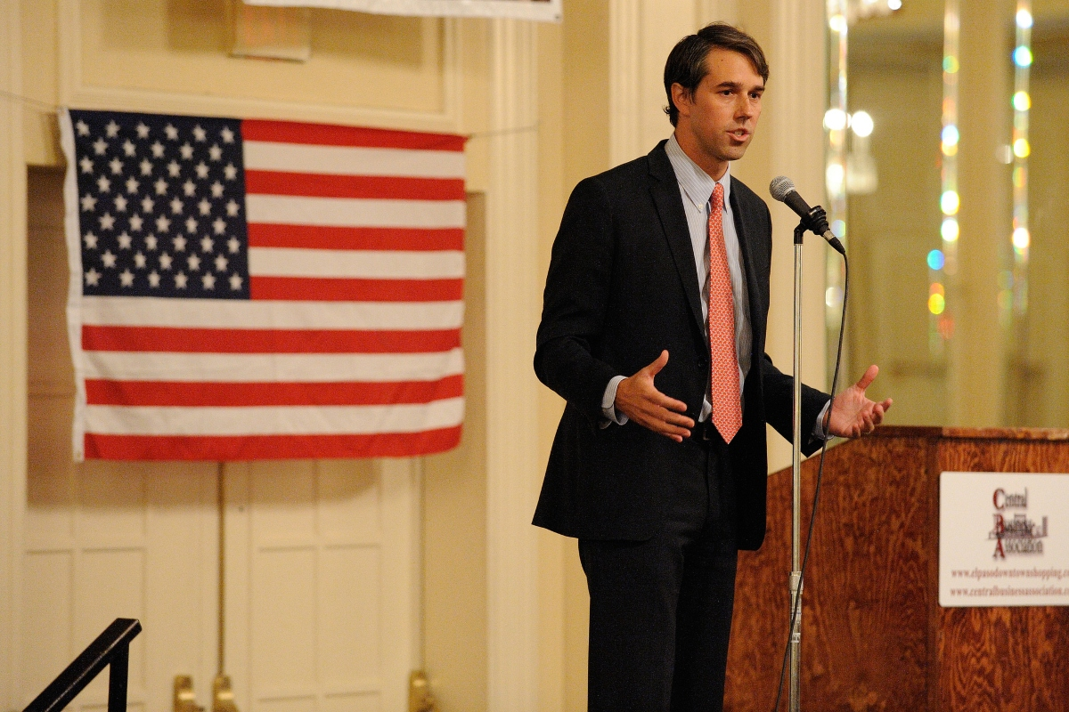 Color photo of Beto O'Rourke speaking at a podium, with an American flag in the background, when he was running for Congress in 2012