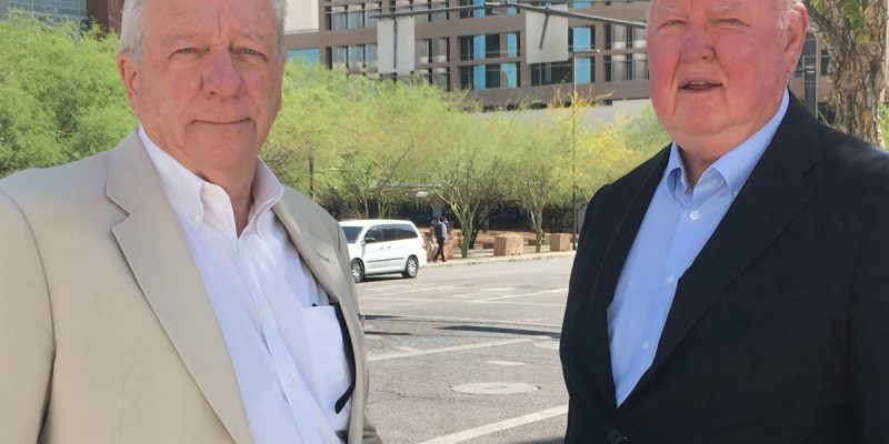 Photo of Michael Lacey and Jim Larkin, wearing sport coats, outside federal court in downtown Phoenix, Arizona.