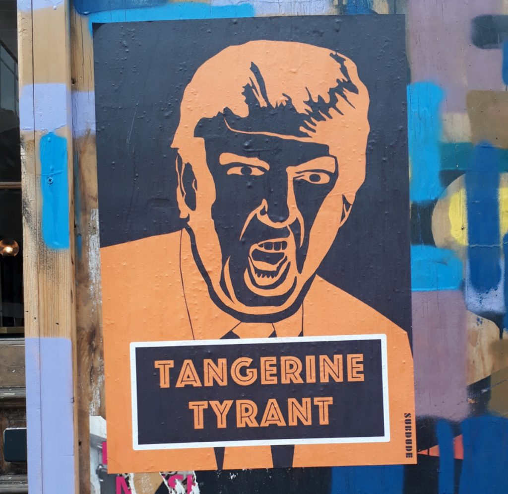 "Photo of a poster of Trump screaming with the title, ""Tangerine Tyrant."""