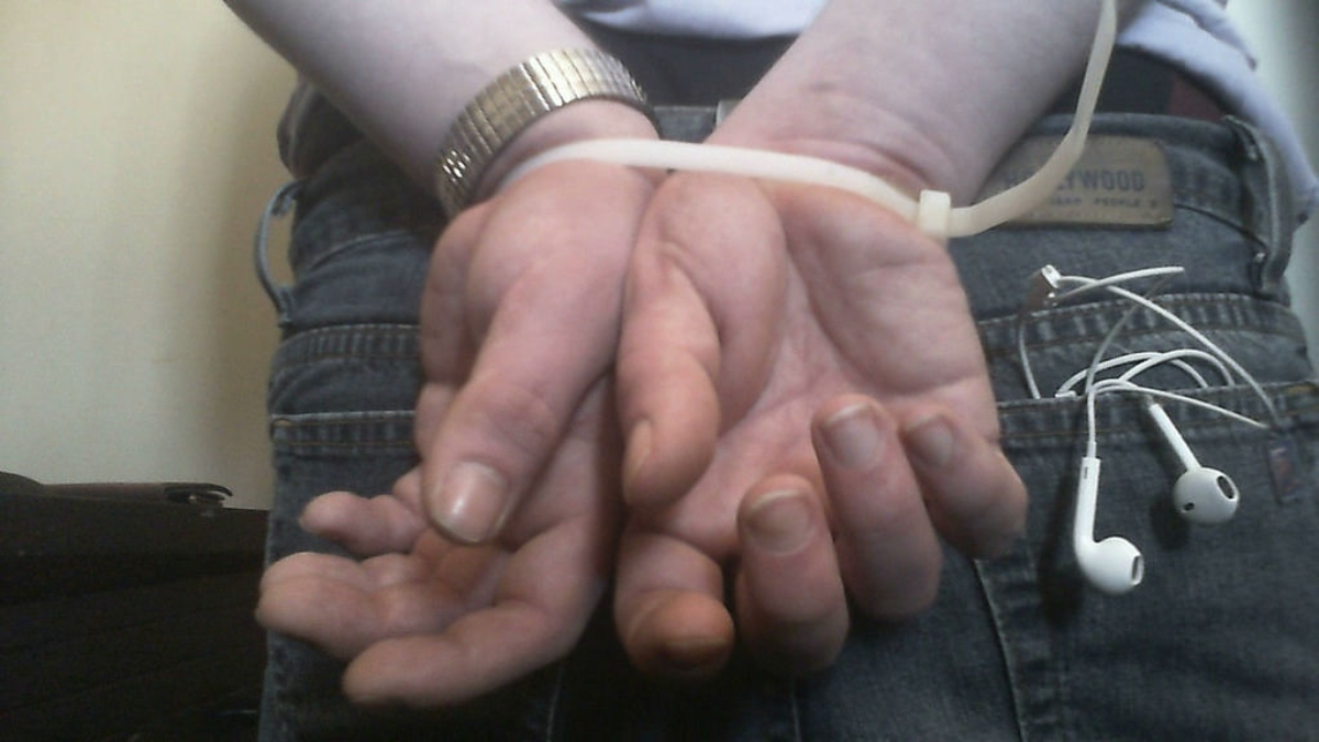 Closeup photo of a man's hands zip-tied behind his back.