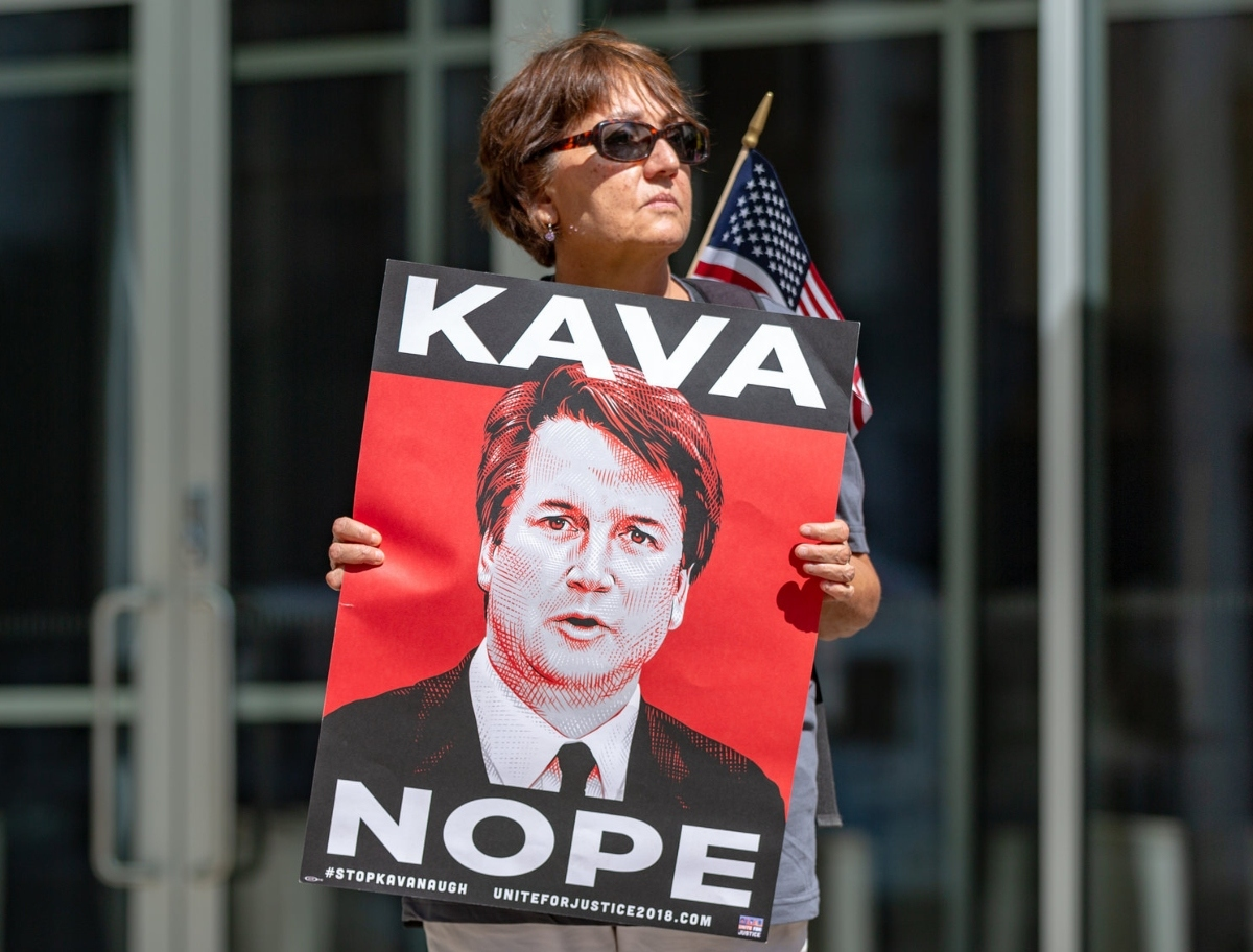 "Photo of a woman holding a poster depicting Judge Brett Kavanaugh, with ""KAVA"" above and ""NOPE"" below"