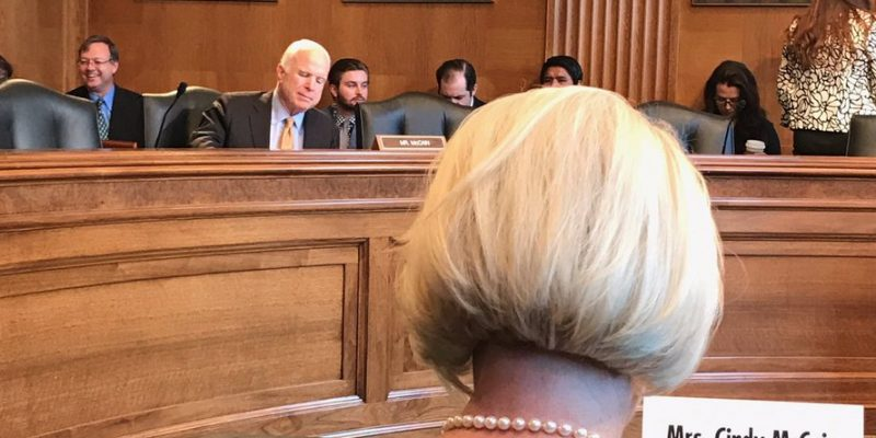 photo of John and Cindy McCain at a 2017 hearing held by the U.S. Senate Committee on Indian Affairs. John McCain is prominent in the background, while Cindy McCain has her back to the camera in the foreground, identifiable by a name placard and her silvery blond hairdo and pearl necklace