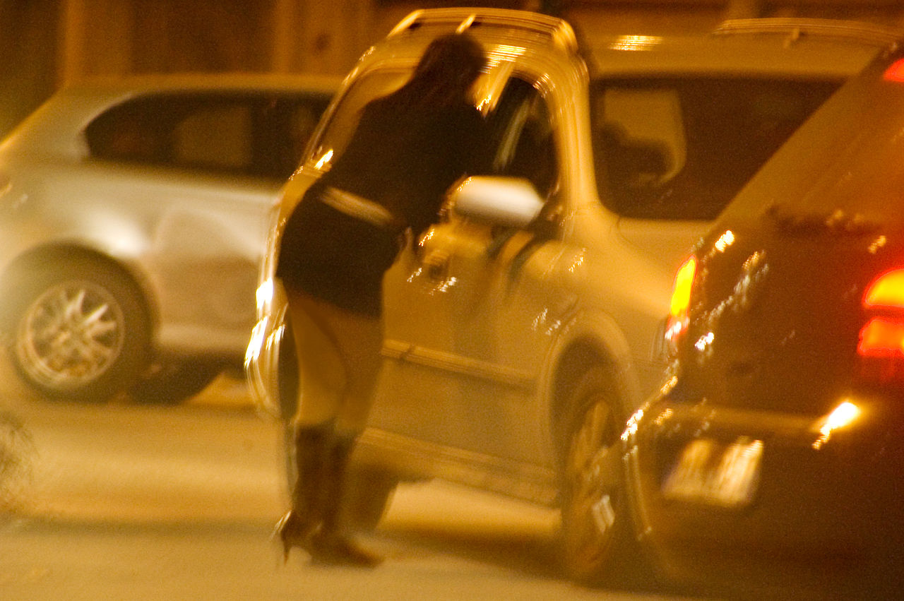 Blurry nighttime photo of streetwalker in short skirt talking to driver of a car in Turin, Italy