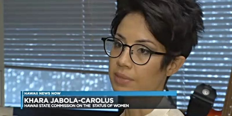 Screenshot of a bespectacled young woman in an office