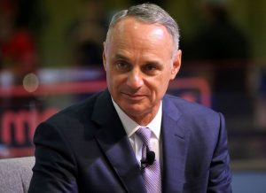 Head-and-shoulders photo of Major League Baseball commissioner Rob Manfred, wearing a dark blue suit, white shirt, and purple tie
