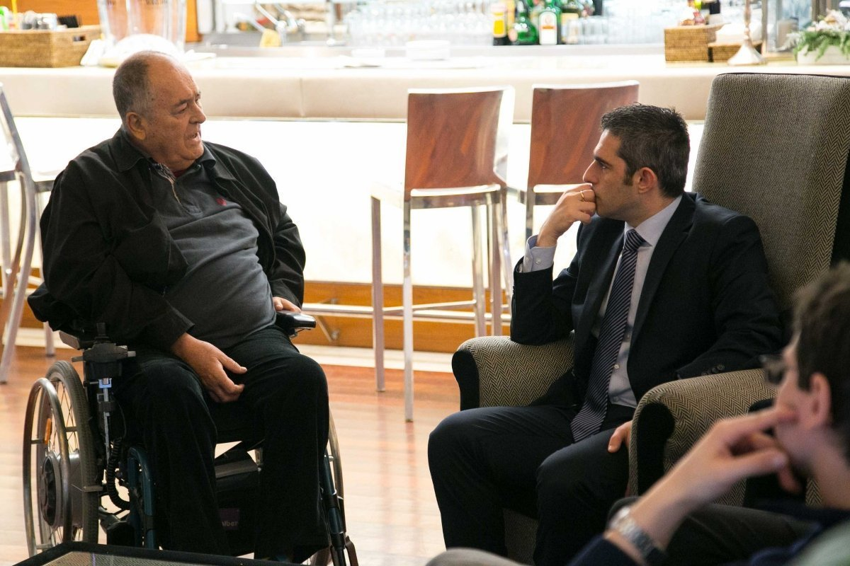 Photo of Bernardo Bertolucci, seated in a wheelchair, talking to another man seated in a chair.