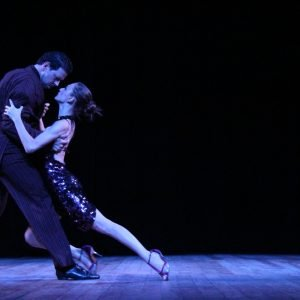 A photo of a man and a woman dancing the tango, locked in a passionate embrace.