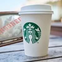 foreground: white to-go cup with Starbucks logo on a wood-plank table. background: vintage TV set showing blurry porn scene, blocked out with a red CENSORED stamp